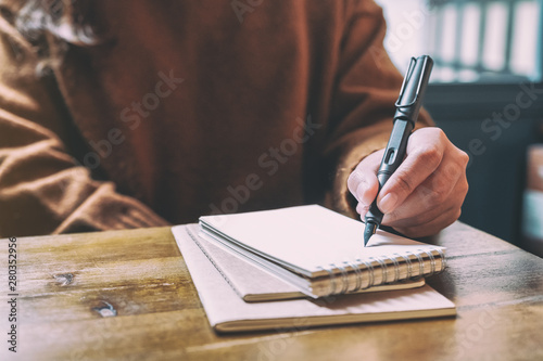 Fotografie, Obraz  Closeup image of a woman writing on blank notebook with fountain pen on wooden t