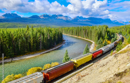 Cadres-photo bureau Route dans la forêt Long freight comtainer train moving along Bow river in Canadian Rockies ,Banff National Park, Canadian Rockies,Canada