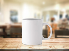 White Coffee Mug Or Drink Cup On Blur Restaurant Or Desserts Cafe Interior Store Background. Wooden Shelf Backdrops With Mugs For Design.