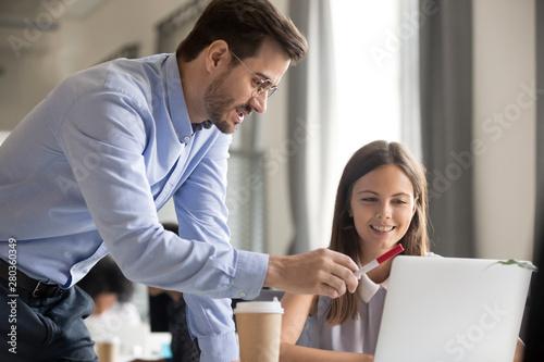 Photo Mentor explaining task to smiling female employee