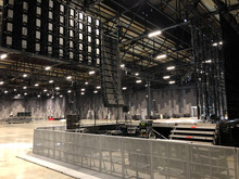Installation Of Professional Sound Speakers, Line Array And Stage Equipment For A Concert. Backstage Area And Tech Zone With Metal Barriers.