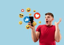 Social Media Interactions On Mobile Phone. Internet Digital Marketing, Chating, Commenting, Liking. Smiles And Icons Above Smartphone Screen, That Holding By Young Man On Blue Studio Background.