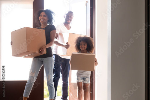 Photo  Happy african family with little daughter arrive at new home