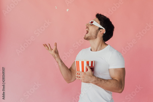 Fototapeta muscular man in 3d glasses throwing up and eating popcorn isolated on pink