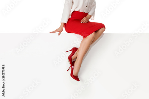 Beautiful legs woman wearing red skirt and high heels shoes sitting on white bench Wallpaper Mural