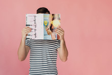 Front View Of Man In Striped T-shirt Reading Magazine Isolated On Pink