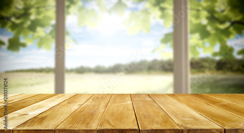 Table background and spring time. Green nature in blurred view in distance. Empty space for decoration and an advertising product.