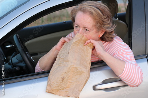 Mature female driver vomiting in paper bag Tapéta, Fotótapéta