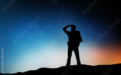 travel, tourism, hike and people concept - silhouette of traveler standing on edge and looking far away over starry night sky or space background