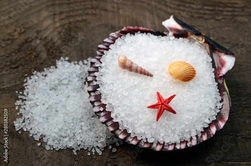 Fotografering  Sea salt in a seashell on old wooden background