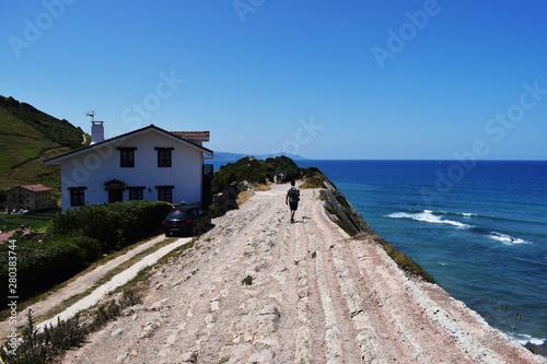 Camino hacia el horizonte del mar con una casa. Wallpaper Mural