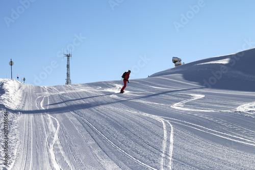 Fotomural  Snowboarder descends on snowy ski slope prepared by snowcat
