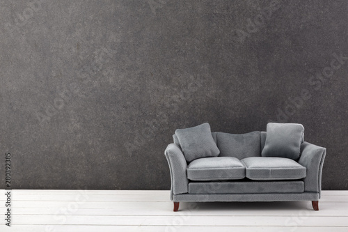 Fototapety, obrazy: Modern grey sofa on grey wall background. Free space