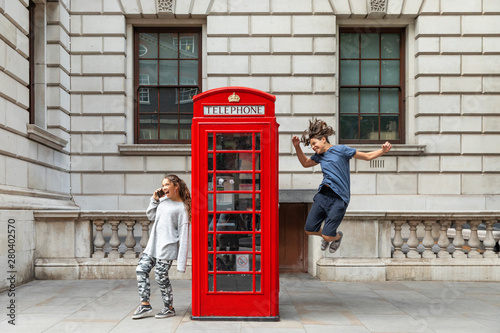 Foto op Plexiglas Londen Girl is leaning against the phone booth with a smartphone and from the other side a boy leaps with joy.