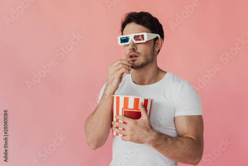 Fotografie, Obraz curious muscular man in 3d glasses eating popcorn isolated on pink