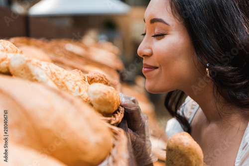 Fototapeta selective focus of cheerful asian woman smiling while smelling bread in supermarket obraz