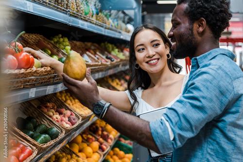 Cuadros en Lienzo  happy asian woman looking at african american man near fruits in store