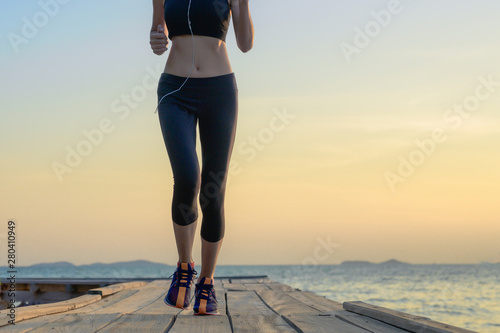 legs of healthy woman jogging alone at daily morning on the wooden jetty bridge or pier, daily exercise workout running at light of sunset, trail running at seaside - 280410949