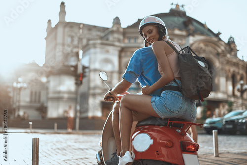 Smiling lady in shorts sitting behind boyfriend on the motorbike Fototapeta
