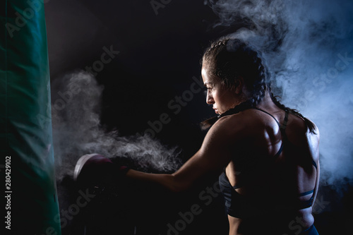 Fotografia  Young female boxer punching a bag on a sports training in a gym.