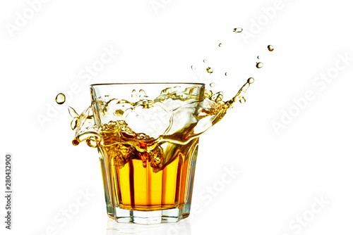 Garden Poster Splashing water whiskey in a glass splash isolated on white background with reflection