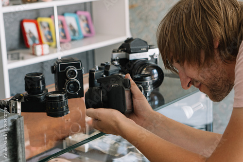 Fototapeta young male photographer takes photographs with a modern digital camera old retro analog film cameras in a shop photo showcase collection obraz na płótnie