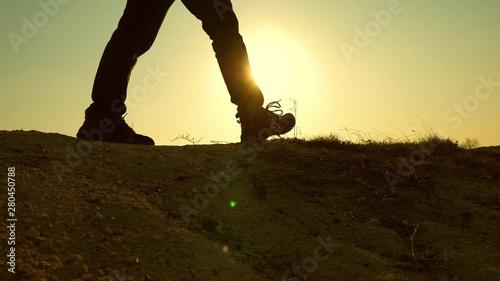 Türaufkleber Pistazie a courageous man-traveler, climbing to top of a mountain, walking along a path along a dangerous rocky ridge. Steep wall that opens a beautiful sunset view. slow motion. close-up.