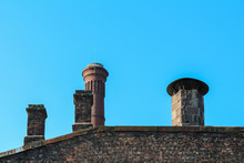 Vintage Chimney Pipes On The Old Roof Of A Brick House