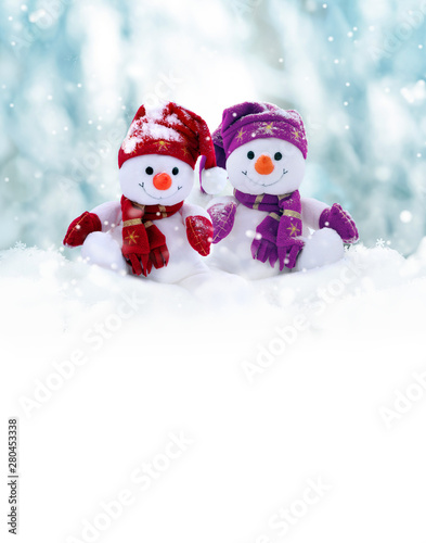 Obraz Two little snowmen the girl and the boy in caps and scarfs on snow in the winter. Background with a funny snowman. Christmas card. - fototapety do salonu