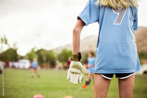 Midsection rear view of female goalie playing soccer on field against sky