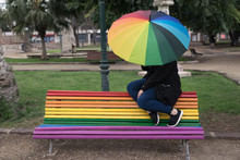 Woman Celebrating Gay Pride Sitting On Rainbow Bench With Rainbow Umbrella