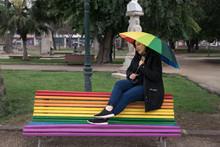 Woman  Sitting On Rainbow Bench With Rainbow Umbrella In The Rain