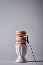 Macarons Stacked In A Egg Cup, Fork On The Side On Gray Background