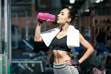 Lifestyle Portrait Of A Young Slim Woman  Drinking Water From Pink Bottle In A Gym