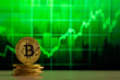Leinwandbild Motiv physical bitcoin standing at a wood table in front of a Green graph. Bitcoin Bull Market concept.