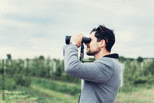 Foto auf Leinwand Olivgrun Portrait of young adventure man travelling with binoculars, watching landscape view outdoors. Young brunette man discover nature scenes. Travelling, discovering, vacation concept
