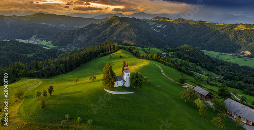 Foto op Aluminium Bomen Skofja Loka, Slovenia - Aerial panoramic view of the beautiful hilltop church of Sveti Tomaz (Saint Thomas) with amazing golden sunset and the Julian Alps at background at summer time