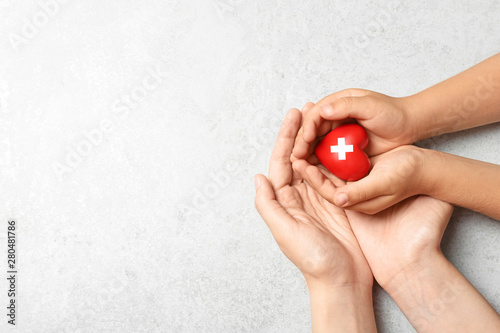 Fotografie, Obraz Woman and child holding heart on grey stone background, top view with space for text
