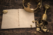 Open Blank Page Book, Golden Crown And A Goblet Full Of Gold On A Wooden Table Background.