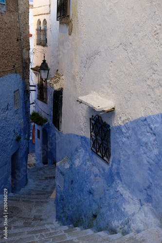 Fototapety, obrazy: narrow spiral down stairs in Chefchaouen Morocco. white and blue colorful painting walls and windows