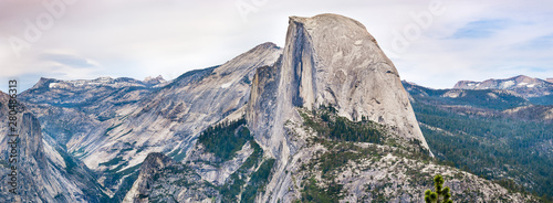 Panoramic view of the majestic Half Dome and the surrounding wilderness area with mountain peaks and ridges still covered by snow; Yosemite National Park, Sierra Nevada mountains, California