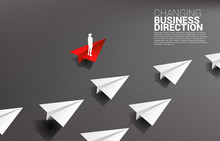 Silhouette Of Businessman Standing On Red Origami Paper Airplane Is Move Apart Direction From Group Of White. Business Concept Of Disruption And Niche Marketing