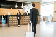 Businessman With Suitcase Walking Towards Clerk In Lobby