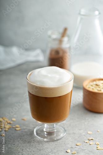 Oat milk latte with thick foam in a glass Fototapet