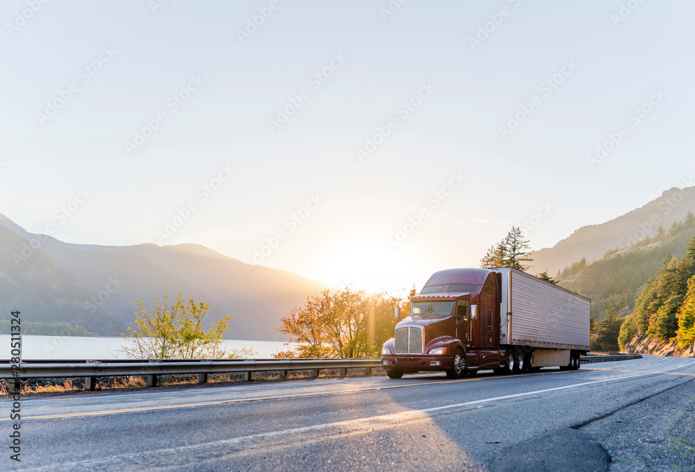 Fototapety, obrazy: Big rig burgundy semi truck transporting commercial cargo in refrigerator semi trailer driving on the road along Columbia River with sunshine