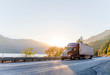 canvas print picture Big rig burgundy semi truck transporting commercial cargo in refrigerator semi trailer driving on the road along Columbia River with sunshine