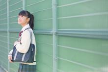 フェンスの前を立つ女子校生