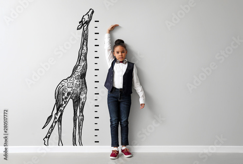 Stampa su Tela Cute little African-American girl measuring height near light wall with drawn gi