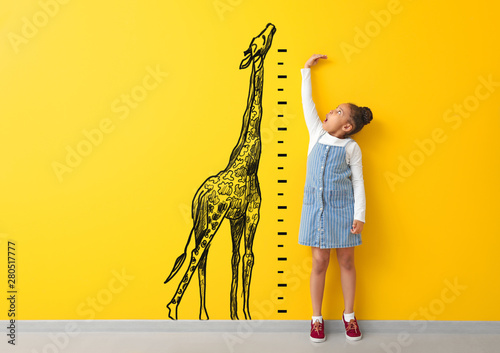Surprised African-American girl measuring height near color wall with drawn gira Wallpaper Mural