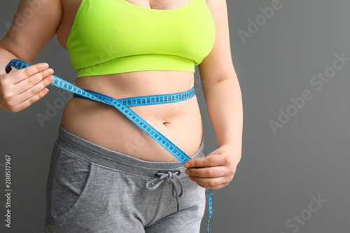 Overweight woman with measuring tape on grey background Fototapete